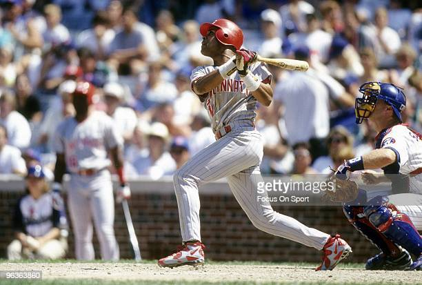 Shortstop Barry Larkin of the Cincinnati Reds swings and watches the flight of his ball against the Chicago Cubs during a circa 1995 MLB baseball...