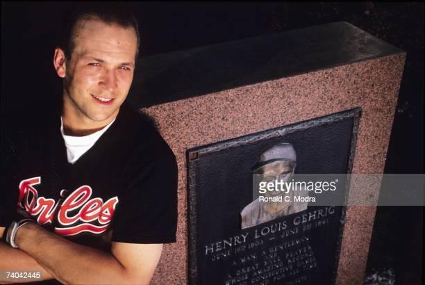 Shortstop Cal Ripken Jr #8 of the Baltimore Orioles leans against Lou Gehrig memorial monument in Yankee Stadium before a June 1990 game