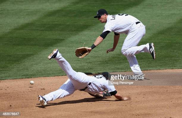 Shortstop Charlie Culberson of the Colorado Rockies and second baseman DJ LeMahieu of the Colorado Rockies can't stop a ground ball by Alexei Ramirez...