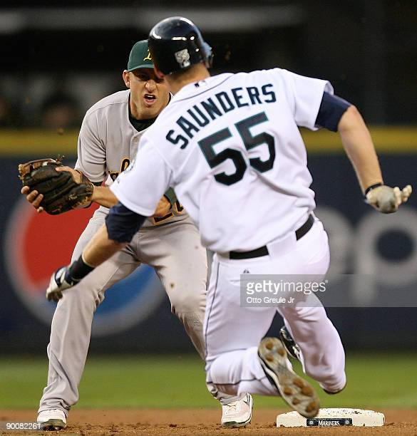 Shortstop Cliff Pennington of the Oakland Athletics waits to tag out Michael Saunders of the Seattle Mariners on a steal attempt at second base on...