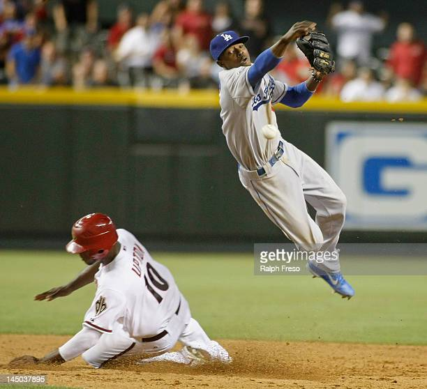 Shortstop Dee Gordon of the Los Angeles Dodgers leaps over Justin Upton of the Arizona Diamondbacks as he throws to first to complete a game ending...