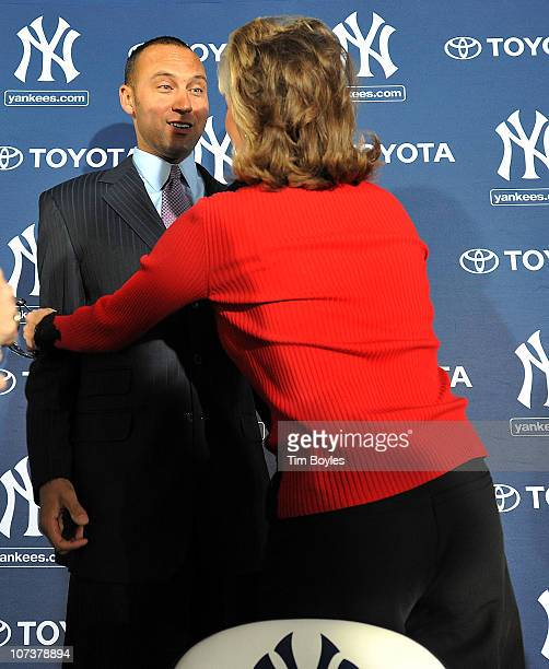 Shortstop Derek Jeter of the New York Yankees gets a hug from Jennifer SteinbrennerSwindal during a press conference to announce his new contract...