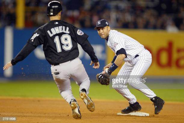 Shortstop Derek Jeter of the New York Yankees looks to turn a double play as Mike Lowell of the Florida Marlins slides into second base during game...