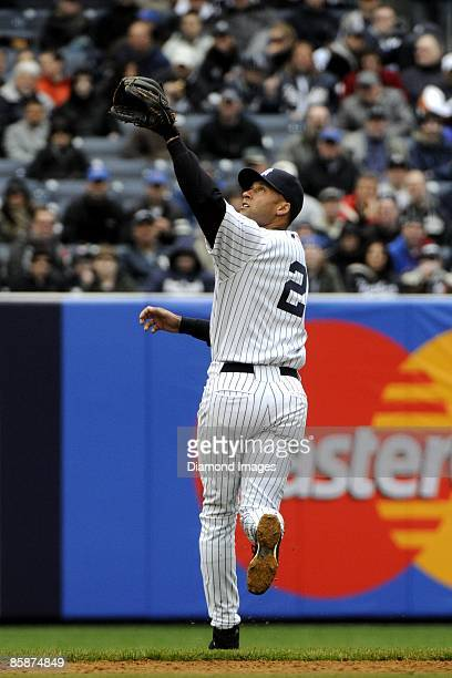 Shortstop Derek Jeter of the New York Yankees reaches for a shallow pop fly ball during an exhibition game on April 4, 2009 against the Chicago Cubs...