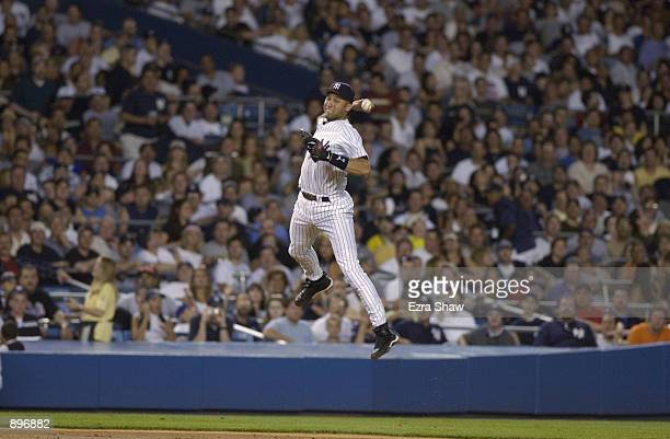Shortstop Derek Jeter of the New York Yankees throws from midair to first base during the MLB game against the New York Mets on June 30 2002 at...