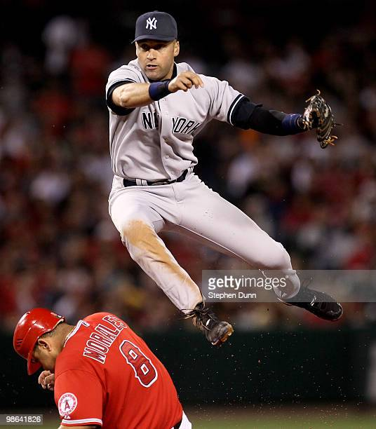 Shortstop Derek Jeter of the New York Yankees throws to first after forcing out Kendry Morales of the Los Angeles Angels of Anaheim to turn a double...