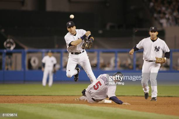 Shortstop Derek Jeter of the New York Yankees tries to make a double play as third baseman Michael Cuddyer of the Minnesota Twins slides into second...