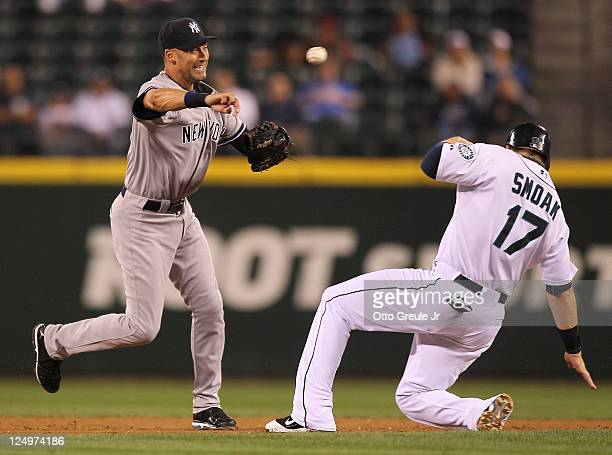 Shortstop Derek Jeter of the New York Yankees turns a double play over Justin Smoak of the Seattle Mariners at Safeco Field on September 14 2011 in...