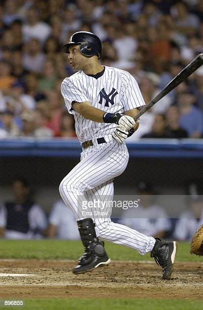 Shortstop Derek Jeter of the New York Yankees watches the flight of the ball during the MLB game against the New York Mets on June 30 2002 at Yankee...