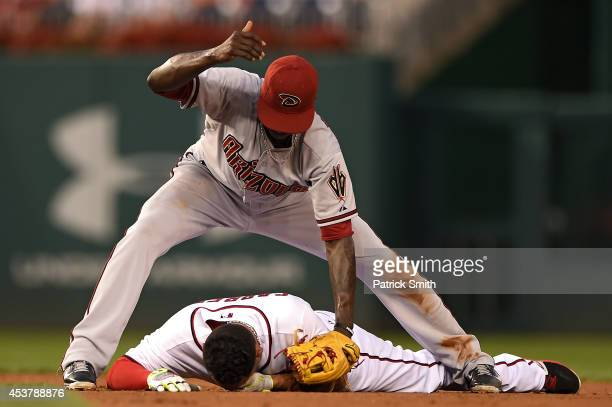 Shortstop Didi Gregorius of the Arizona Diamondbacks signals to the dugout for help after colliding with Asdrubal Cabrera of the Washington Nationals...