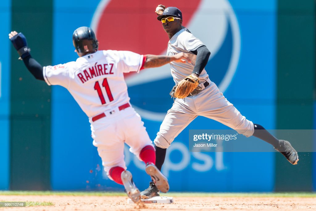 Shortstop Didi Gregorius #18 of the New York Yankees throws out Yonder Alonso #17 of the Cleveland Indians at first as Jose Ramirez #11 is out at second for a double play to end the seventh inning at Progressive Field on July 15, 2018 in Cleveland, Ohio.