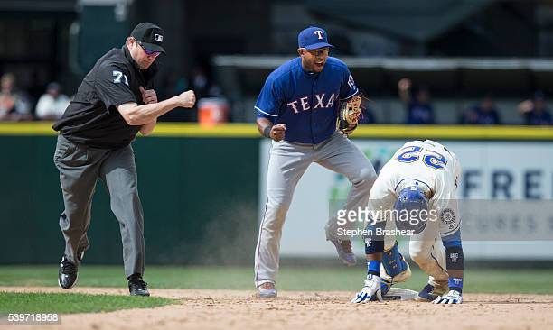 Shortstop Elvis Andrus, center, celebrates a victory after tagging out Robinson Cano of the Seattle Mariners at second base while second base umpire...