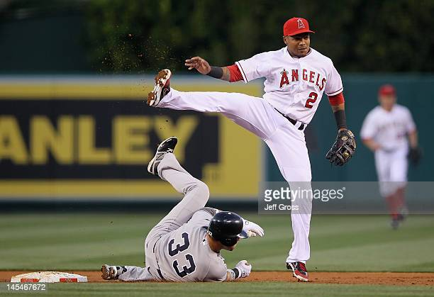 Shortstop Erick Aybar of the Los Angeles Angels of Anaheim forces Nick Swisher of the New York Yankees out at second base before throwing to first to...