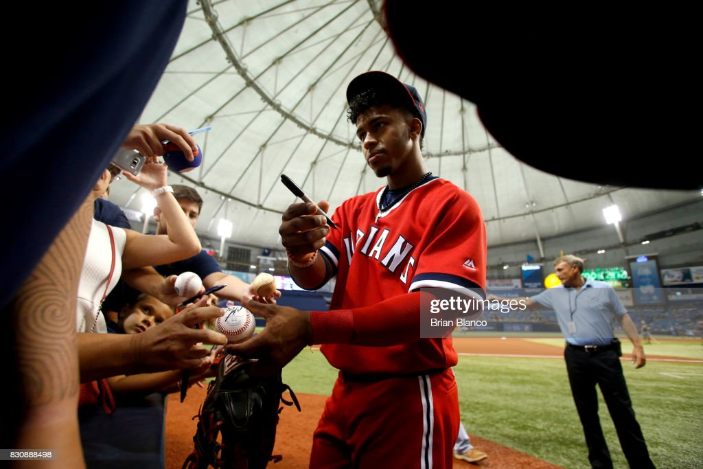 Shortstop Francisco Lindor #12 of the Cleveland Indians signs autographs for fans before the start of a game Tampa Bay Rays on August 12, 2017 at Tropicana Field in St. Petersburg, Florida.