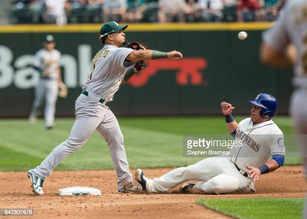 Shortstop Franklin Barreto of the Oakland Athletics turns a double play after forcing out Carlos Ruiz of the Seattle Mariners at second base on a...
