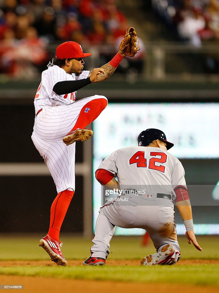 Shortstop Freddy Galvis, left, of the Philadelphia Phillies jumps to avoid contact by Wilson Ramos, right, of the Washington Nationals on a fielders choice hit by Danny Espinosa in the third inning during an MLB game at Citizens Bank Park on April 15, 2016 in Philadelphia, Pennsylvania. All players are wearing #42 in honor of Jackie Robinson.