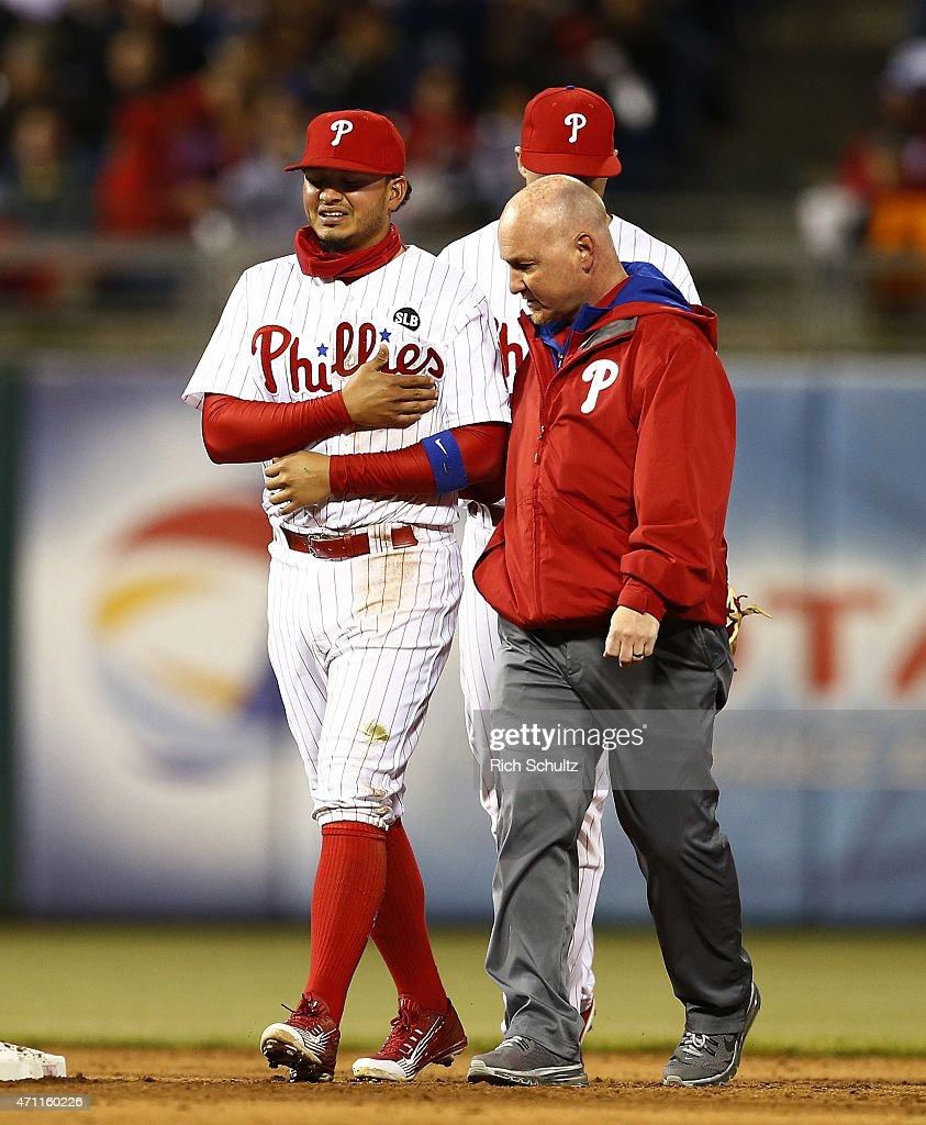 Shortstop Freddy Galvis #13 of the Philadelphia Phillies walks off the field with a team trainer after making a great play and throw to first base to get Nick Markakis #22 of the Atlanta Braves during the sixth inning of a game at Citizens Bank Park on April 24, 2015 in Philadelphia, Pennsylvania. Galvis remained in the game as the Braves defeated the Phillies 5-3.