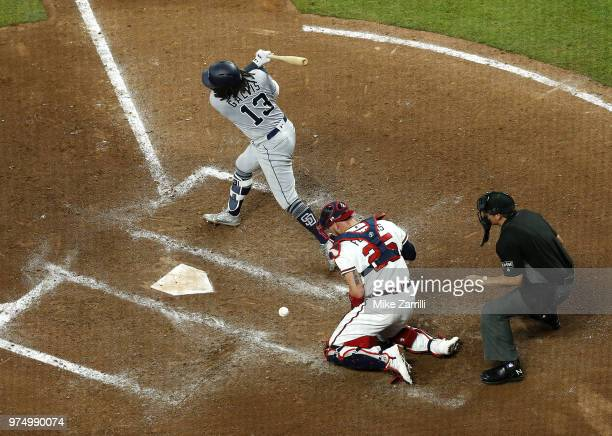 Shortstop Freddy Galvis of the San Diego Padres strikes out in the seventh inning and catcher Tyler Flowers of the Atlanta Braves blocks the pitch...