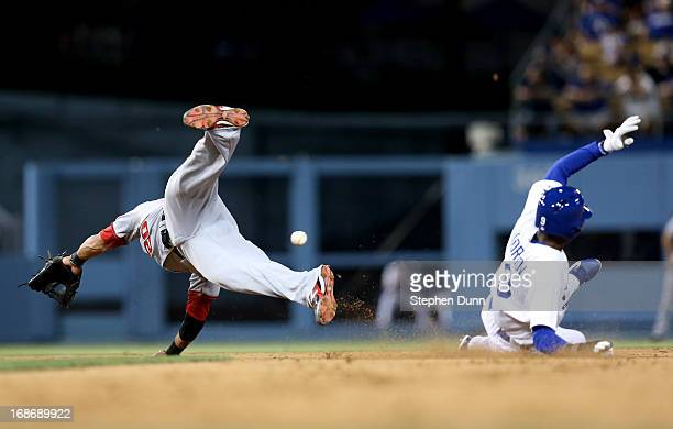 Shortstop Ian Desmond of the Washington Nationals dives for an errant throw as Dee Gordon of the Los Angeles Dodgers slides into second with a stolen...