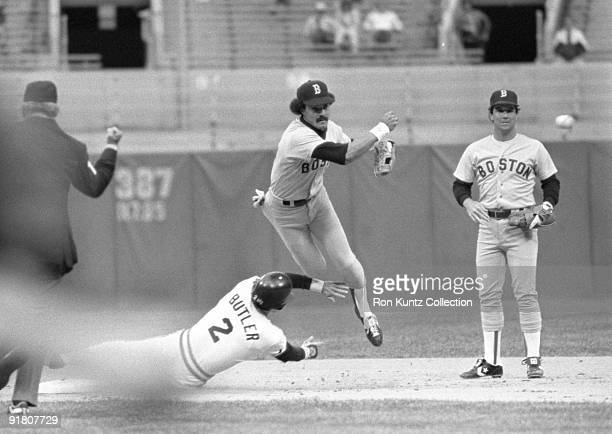 Shortstop Jackie Gutierrez of the Boston Red Sox turns the double play as outfielder Brett Butler of the Cleveland Indians tries to break up the play...