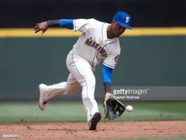 Shortstop Jean Segura of the Seattle Mariners fields a ground ball hit by Ian Desmond of the Colorado Rockies before throwing first base for an out...