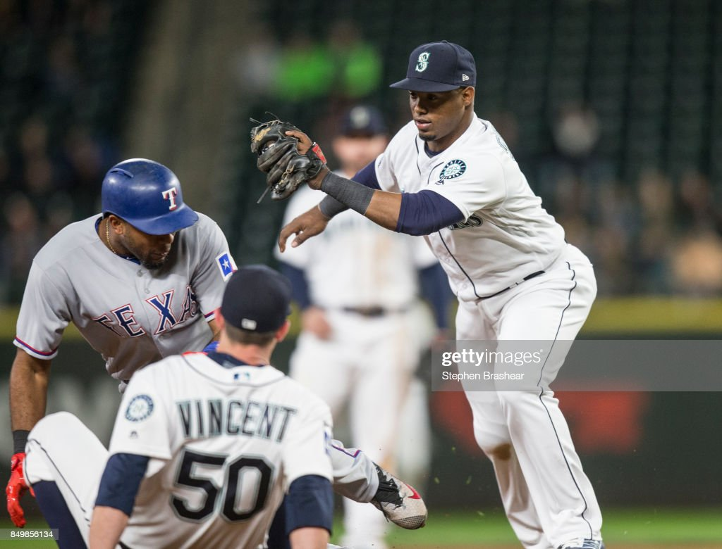 Shortstop Jean Segura #2 of the Seattle Mariners tries to tags out Elvis Andrus #1 of the Texas Rangers, who was caught stealing third base, as relief pitcher falls to the ground during the eighth inning of a game at Safeco Field on September 19, 2017 in Seattle, Washington. Anrus was ruled out after leaving the base path. The Rangers won the game 3-1.