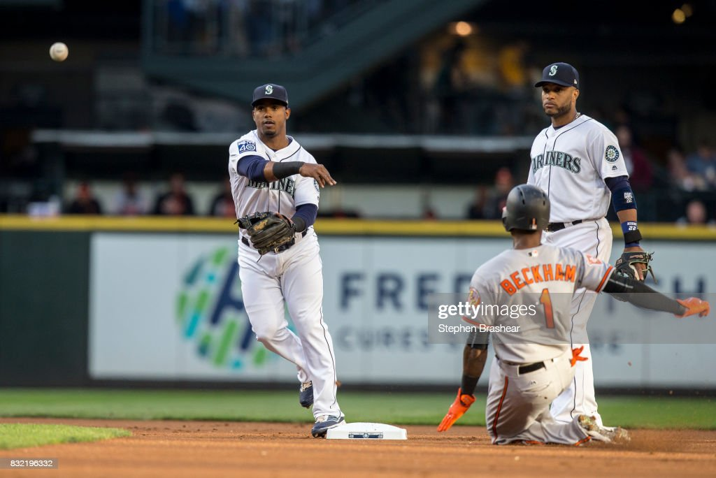 Shortstop Jean Segura #2 of the Seattle Mariners turns a double play after forcing out Tim Beckham #1 of the Baltimore Orioles at second base on a ball hit by Manny Machado #13 of the Baltimore Orioles during the first inning of a game at Safeco Field on August 15, 2017 in Seattle, Washington. At right is second baseman Robinson Cano #22 of the Seattle Mariners.