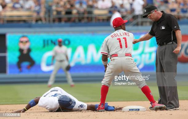Shortstop Jimmy Rollins of the Philadelphia Phillies argues with second base umpire Dale Scott after Scot called Yasiel Puig of the Los Angeles...