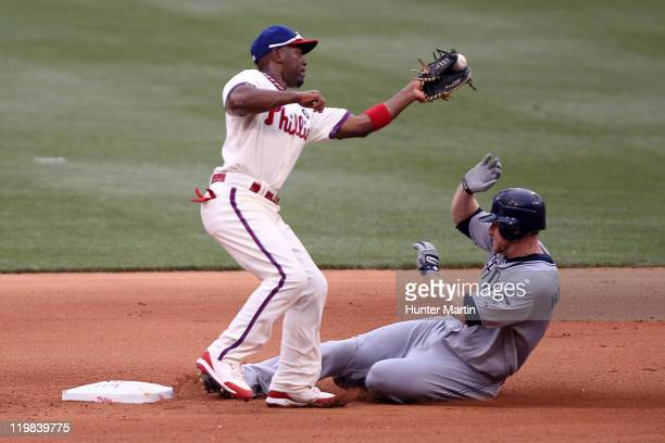 Shortstop Jimmy Rollins of the Philadelphia Phillies attempts to tag out third baseman Chase Headley of the San Diego Padres during a game at...