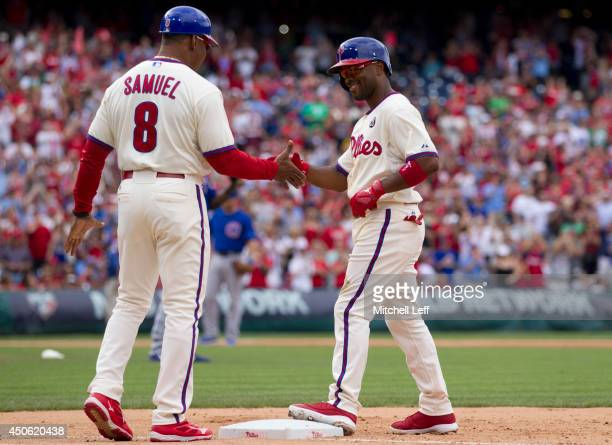 Shortstop Jimmy Rollins of the Philadelphia Phillies hits a single in the bottom of the fifth inning against the Chicago Cubs and is congraulated by...