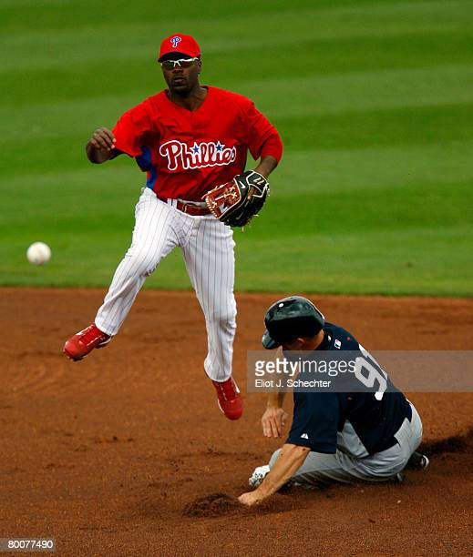 Shortstop Jimmy Rollins of the Philadelphia Phillies throws the ball to first after tagging out Center fielder Brett Gardner of the New York Yankees...