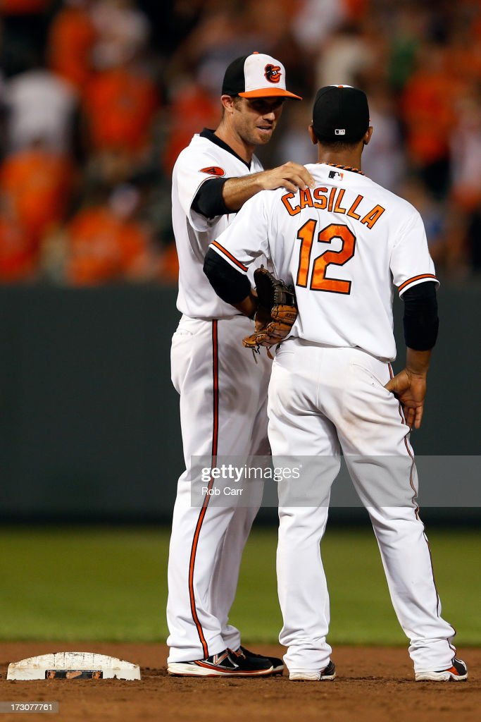 Shortstop J.J. Hardy #2 congratulates teammate Alexi Casilla #12 of the Baltimore Orioles after the Orioles defeated the Cleveland Indians at Oriole Park at Camden Yards on June 25, 2013 in Baltimore, Maryland.