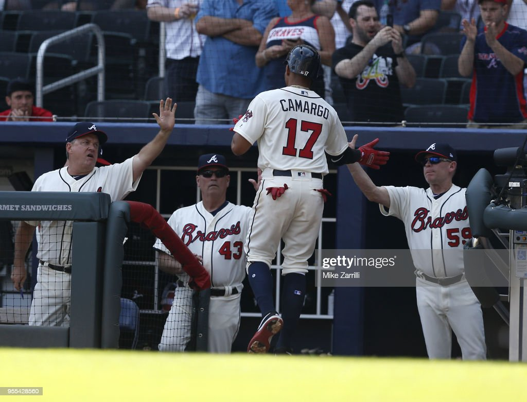 Shortstop Johan Camargo #17 of the Atlanta Braves is congratulated in the dugout after scoring in the ninth inning during the game against the San Francisco Giants at SunTrust Park on May 6, 2018 in Atlanta, Georgia.