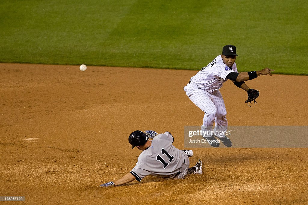 Shortstop Jonathan Herrera #18 of the Colorado Rockies makes a throw to first base to complete the inning ending double play as Brett Gardner #11 of the New York Yankees slides in during the seventh inning at Coors Field on May 7, 2013 in Denver, Colorado. The Rockies defeated the Yankees 2-0.