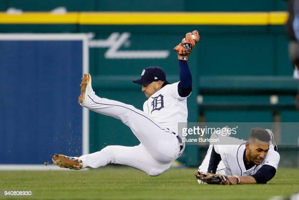 Shortstop Jose Iglesias of the Detroit Tigers falls to the ground after colliding with left fielder Victor Reyes of the Detroit Tigers after catching...
