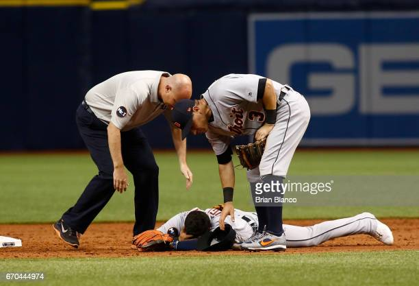 Shortstop Jose Iglesias of the Detroit Tigers is checked on by second baseman Ian Kinsler and a member of the Tigers' medical staff after being...