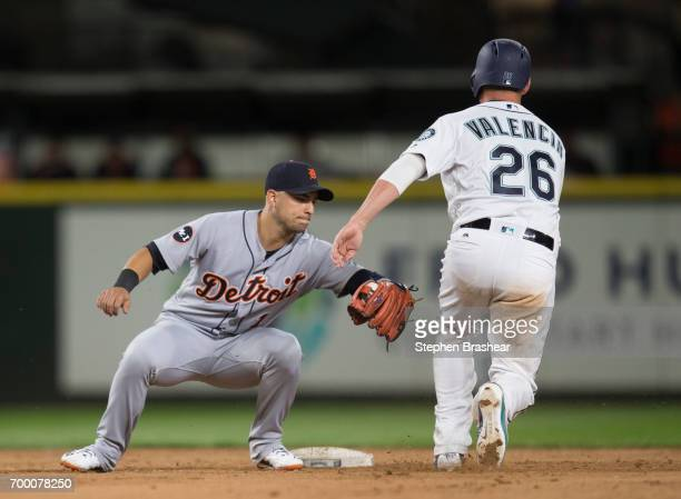 Shortstop Jose Iglesias of the Detroit Tigers tags out Danny Valencia of the Seattle Mariners to complete a double play on a ball hit by Ben Gamel of...