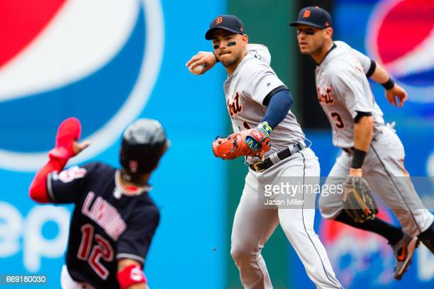 Shortstop Jose Iglesias of the Detroit Tigers throws out Michael Brantley of the Cleveland Indians at first as Francisco Lindor of the Cleveland...