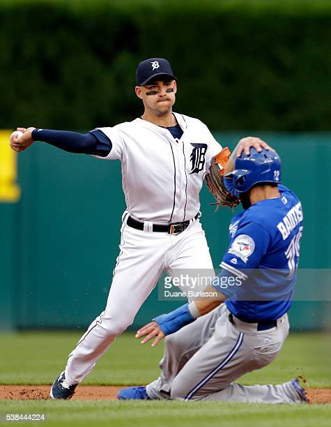 shortstop Jose Iglesias of the Detroit Tigers turns the ball after getting a force out on Jose Bautista of the Toronto Blue Jays at second base...