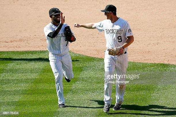 Shortstop Jose Reyes of the Colorado Rockies and second baseman DJ LeMahieu of the Colorado Rockies celebrate after they teamed up with Ben Paulsen...