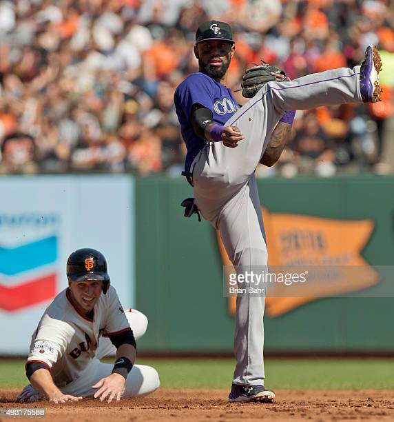Shortstop Jose Reyes of the Colorado Rockies catches Buster Posey of the San Francisco Giants in a fielder's choice at second base and throws to...