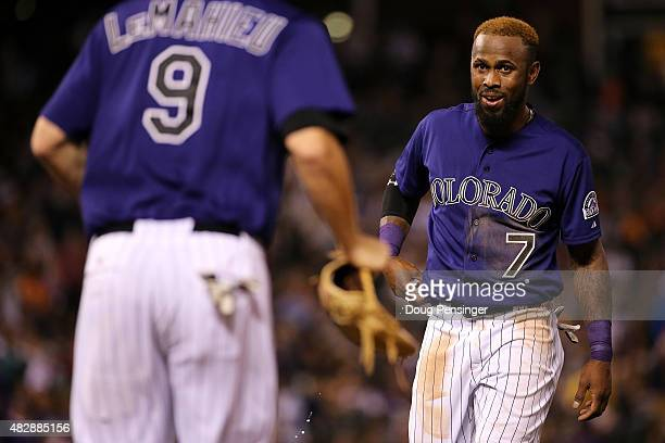 Shortstop Jose Reyes of the Colorado Rockies collects his glove from second baseman DJ LeMahieu of the Colorado Rockies as they take the field...