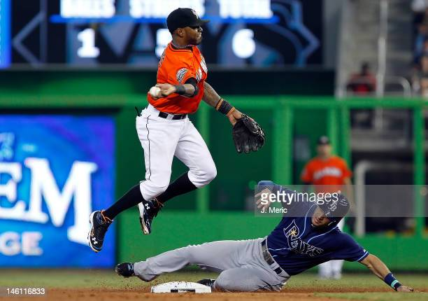 Shortstop Jose Reyes of the Miami Marlins turns a double play as Sean Rodriguez of the Tampa Bay Rays tries to break it up during the interleague...