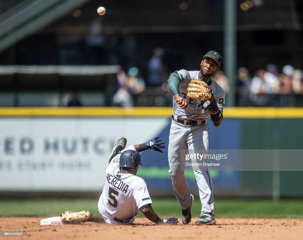 Shortstop Jurickson Profar #19 of the Texas Rangers tries to turn a double play after forcing out Guillermo Heredia #5 of the Seattle Mariners at first base on a fielder's choice hit by Denard Span #4 of the Seattle Mariners during the sixth inning of a game at Safeco Field on May 28, 2018 in Seattle, Washington. The Mariners won the game 2-1. MLB players across the league are wearing special uniforms to commemorate Memorial Day.