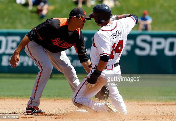 Shortstop Manny Machado of the Baltimore Orioles applies the tag to Martin Prado of the Atlanta Braves on a steal attempt during a Grapefruit League...