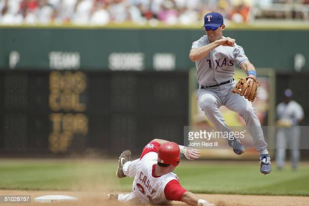 Shortstop Michael Young of the Texas Rangers attempts the double play as Sean Casey of the Cincinnati Reds slides into second base during the MLB...