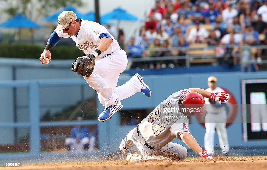 Shortstop Nick Punto #7 of the Los Angeles Dodgers jumps over C.J. Wilson #33 of the Los Angeles Angels of Anaheim after getting a force on a fielder's choice in the second inning at Dodger Stadium on May 27, 2013 in Los Angeles, California.