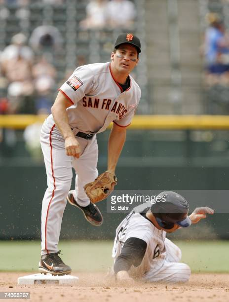 Shortstop Omar Vizquel of the San Francisco Giants throws to first base for a double play against Omar Quintanilla of the Colorado Rockies in the...