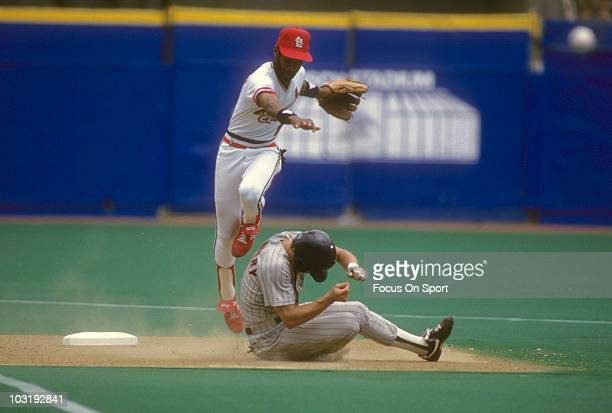 Shortstop Ozzie Smith of the St Louis Cardinals gets his throw off to first avoiding the slide of Tim Flannery of the San Diego Padres circa 1988...