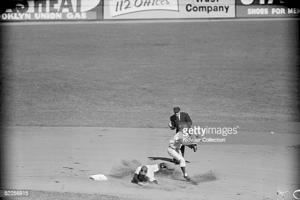Shortstop Pee Wee Reese of the Brooklyn Dodgers attempts to turn the double play as Hank Bauer of the New York Yankees slides into second base during...